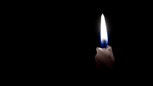 Ein Kerze brennt im Dunkeln.