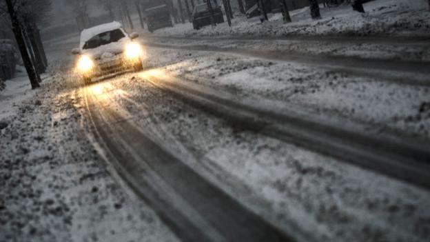 Auto in Winterdämmerung fährt auf kurviger Waldstrasse