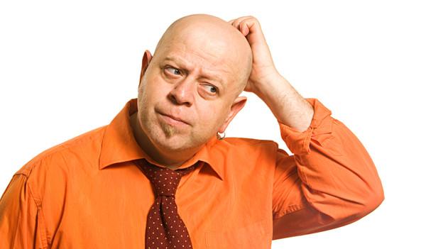 Mann kratzt sich am Kopf und sinniert.