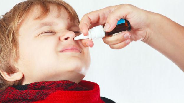 Kind erhält Nasenspray.