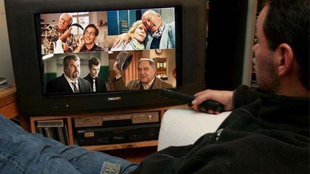 Mann sitzt vor dem Fernseher und schaut Serien.