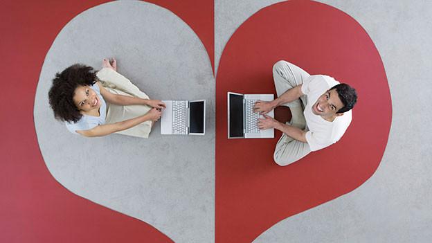 Zwei liegen am Boden vor einem Computer.