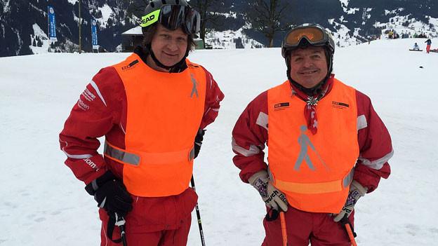 Zwei Skifahrer in oranger Weste auf der Piste.