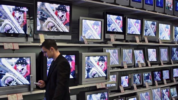 Ein Mann steht im Supermarkt vor einem Regal mit unzähligen Fernsehgeräten.