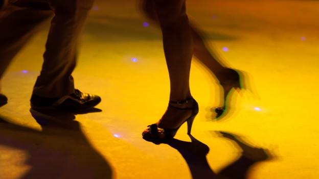Die Beine eines tanzenden Paares auf der Tanzfläche