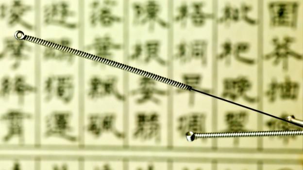 Akupunktur-Nadeln vor Hintergrund mit chinesischen Zeichen.