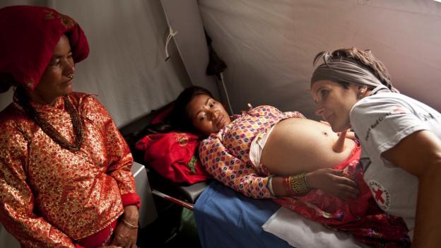 Die Walliser Hebamme Augusta Theler lauscht, was für Geräusche sie im Bauch einer schwangeren Frau hört.