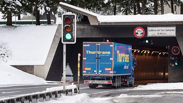 Ein Lastwagen ist kurz vor dem Tunneleingang auf der Autobahn unterwegs.