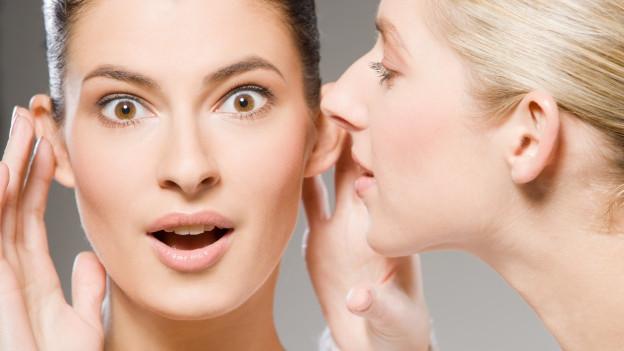 Eine Frau flüstern der anderen Frau mit vorgehaltener Hand ein Gerücht ins Ohr.