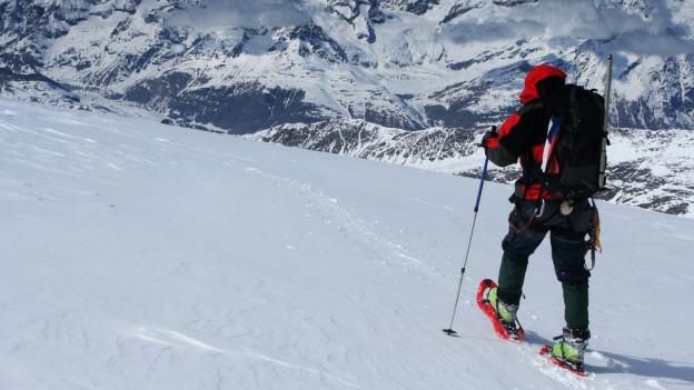 Person mit Schneeschuhen läuft mit Stöcken eine Route ab.