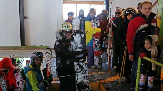 Eine Gruppe von Leuten mit Snowboards und Skiern in Wintersportbekleidung.