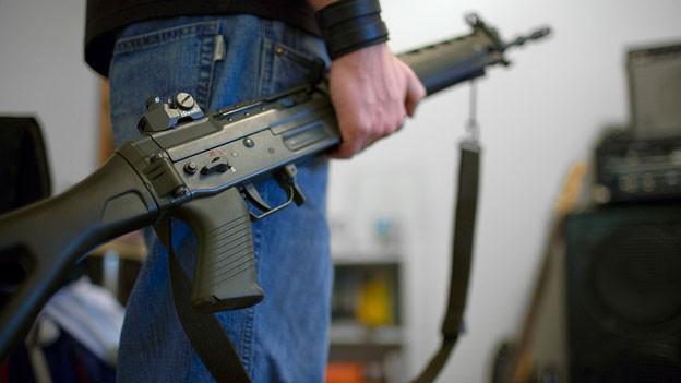 Ein Mann trägt ein Sturmgewehr in der Hand.