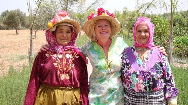 Christine Ferrari steht mit zwei marokkanischen Arbeiterinnen in ihrem botanischen Garten.