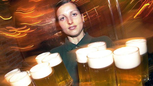 Frau trägt verschiedene Bierhumpen.