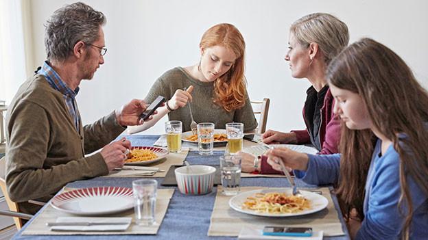 Familie beim Essen. Vater hält ein Samartphone in den Händen.