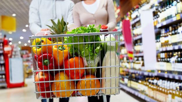 Ein Paar stösst einen Einkaufswagen, gefüllt mit Obst und Gemüse.
