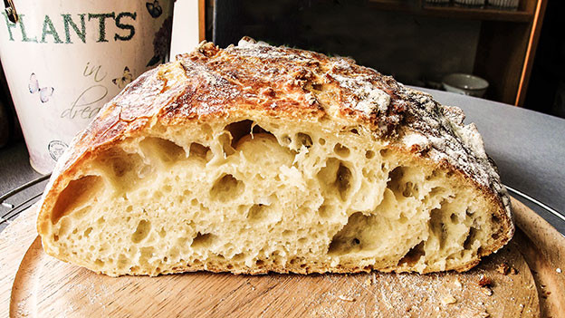 Aufgeschnittenes Brot auf einem Holzbrett.