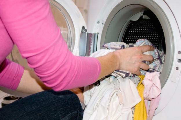Jemand nimmt Wäsche aus der Waschtrommel