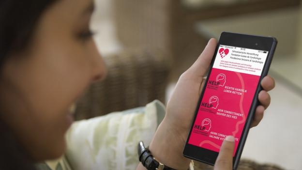 Frau hält Smartphone mit Notfall-App