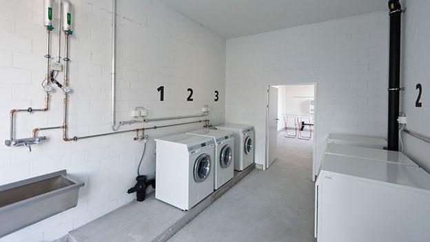 Blick in eine Waschküche mit drei Maschienen.