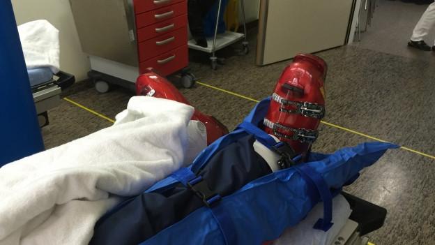Ein eingeschientes Bein auf einer Spitalbahre, die Skihose ist noch an, die Skischuhe noch am Fuss.