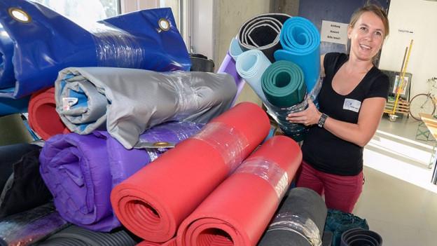 Frau mit Container voller Matten und Schlafsäcken.