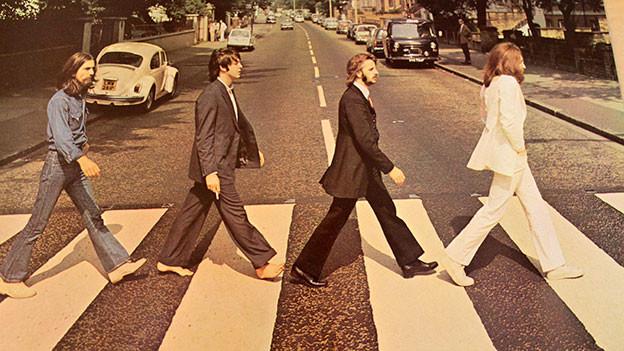 Cover von «Abbey Road». Beatles laufen über Fussgänger-Streifen.