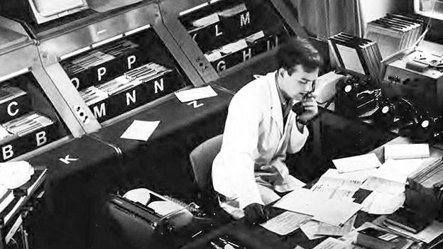 Schwarzweiss Aufnahme vom Tox-Zentrum in seinen Anfängen. Mann in weissem Kittel am Telefon.