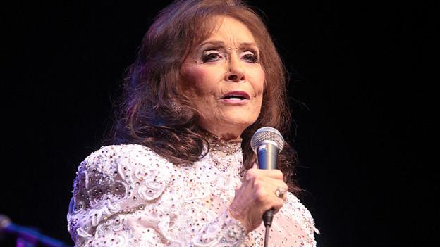 Loretta Lynn im weissen Kleid auf der Bühne.