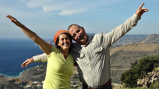 Sonja Roost-Weideli und Rolf Roost stehen auf einem Aussichtspunkt in Gythion und strecken die Arme aus.