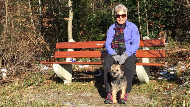 Frau und Hund sitzen auf einer Bank an der Sonne.