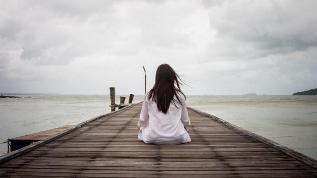 Eine junge Frau sitzt auf einem Holzsteg am Meer.