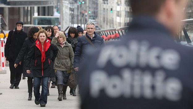 Polizei in Brüssel. Passanten laufen vorbei.