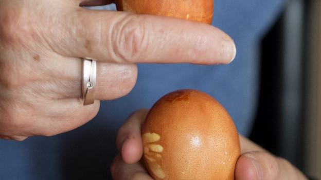 Eine Frau und ein Junge tütschen ein Ei an Ostern