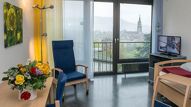 Bild eines Zimmers mit Blumenstrauss, aus dem Fenster geniesst man den Blick aufs Berner Münster.