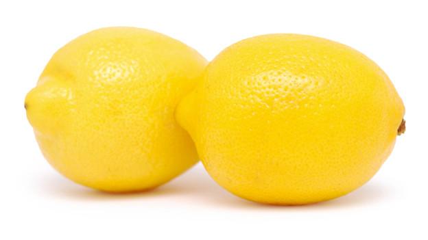 Zwei Zitronen vor weissem Hintergrund.