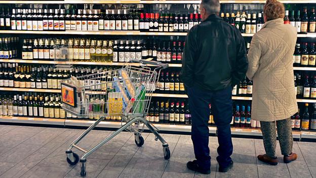 Zwei Menschen stehen vor einem Weinregal.