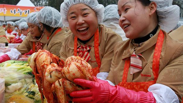Frauen halten marinierten Kohl in den Händen.