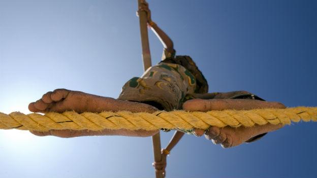 Mädchen geht barfuss über ein Seil. Blick von unten.