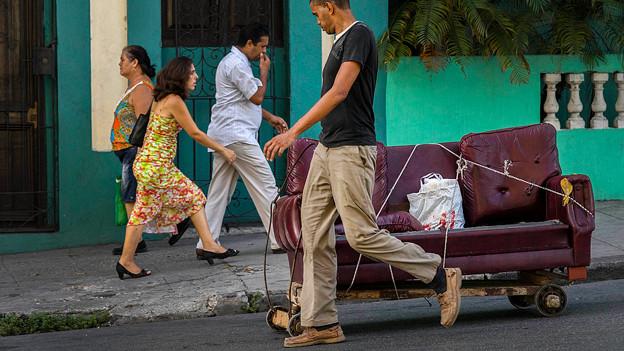 Ein Mann schiebt ein Sofa auf Rollen über die Strasse.