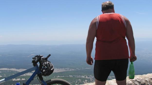Ein übergewichtiger Mann steht neben einem liegenden Fahrrad.