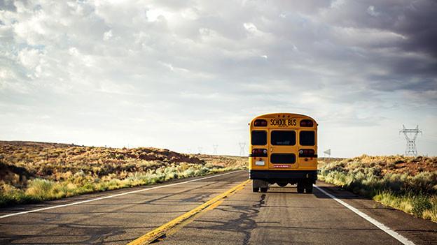 Amerikanischer Schulbus fährt durch Landschaft.