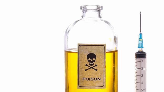 Eine Flasche mit Totenkopf darauf, daneben eine Spritze.