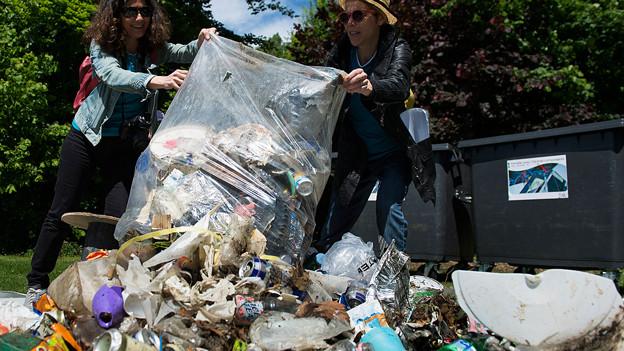 Freiwillige werfen am Seeufer Abfall in einen Müllsack.