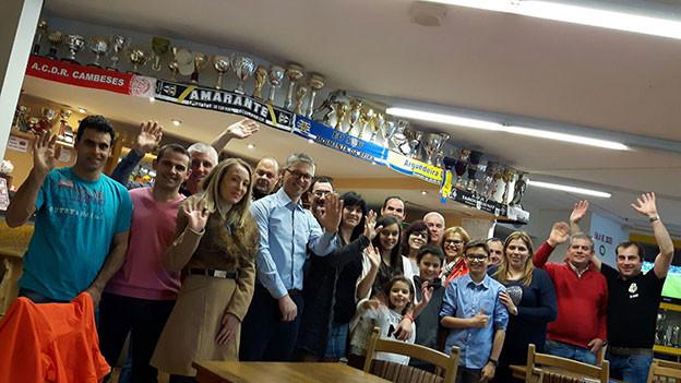 Viele Portugiesen posieren in ihrem Club vor Pokalen.