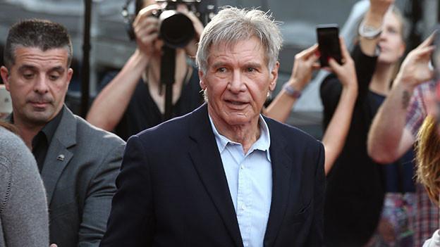 Schauspieler Harrison Ford umringt von Fotografen.
