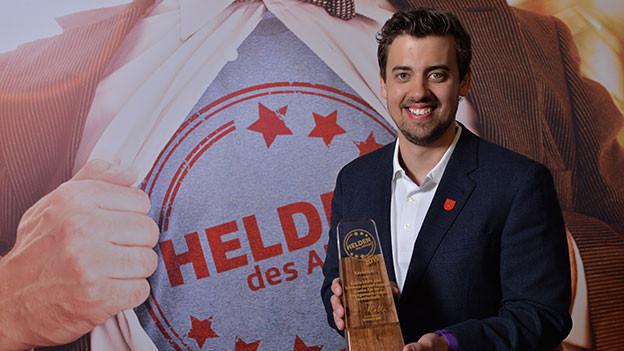«Held des Alltags», Kevin Hirt, hält seinen Ehrenpreis in den Händen.