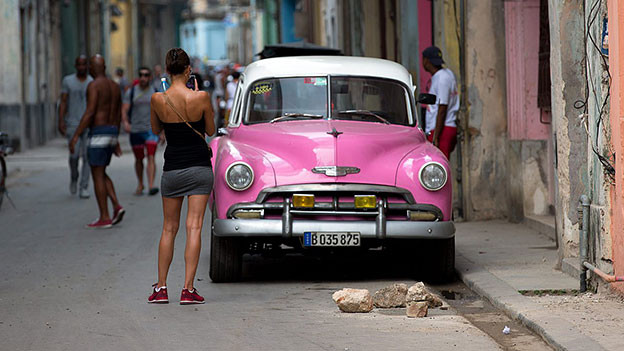 Frau fotografiert Auto in Kuba.