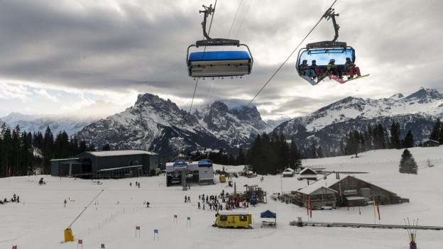 Blick auf Sessel der Bergbahn auf dem Hasliberg mit Gipfeln der Berner Alpen