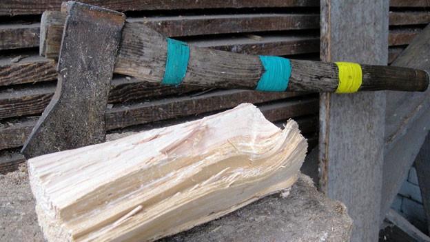 Axt ist auf einem Stück Holz eingeschlagen.
